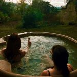 2 women in a hot tub admiring the view with a glass of bubbly